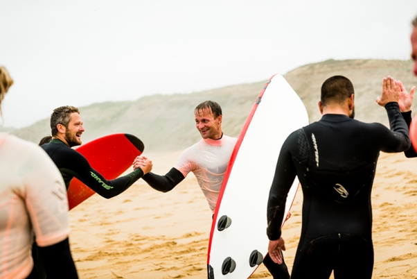 Men high fiving holding surf boards on the beach
