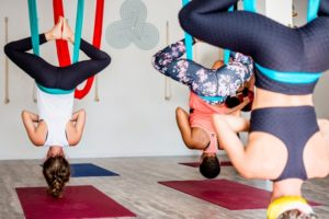 women hanging from ceiling in yoga pose in studio