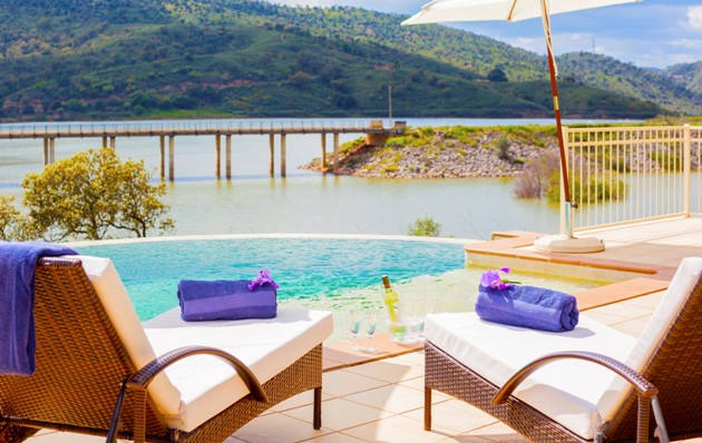 Loungers and wine cooler by infinity pool on the river