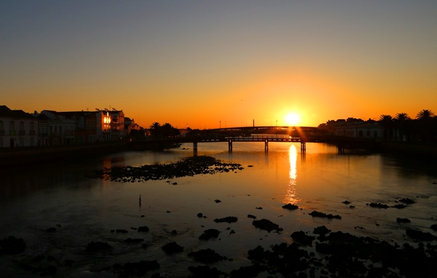 Sunset over bridge in town of Tavira in Portugal