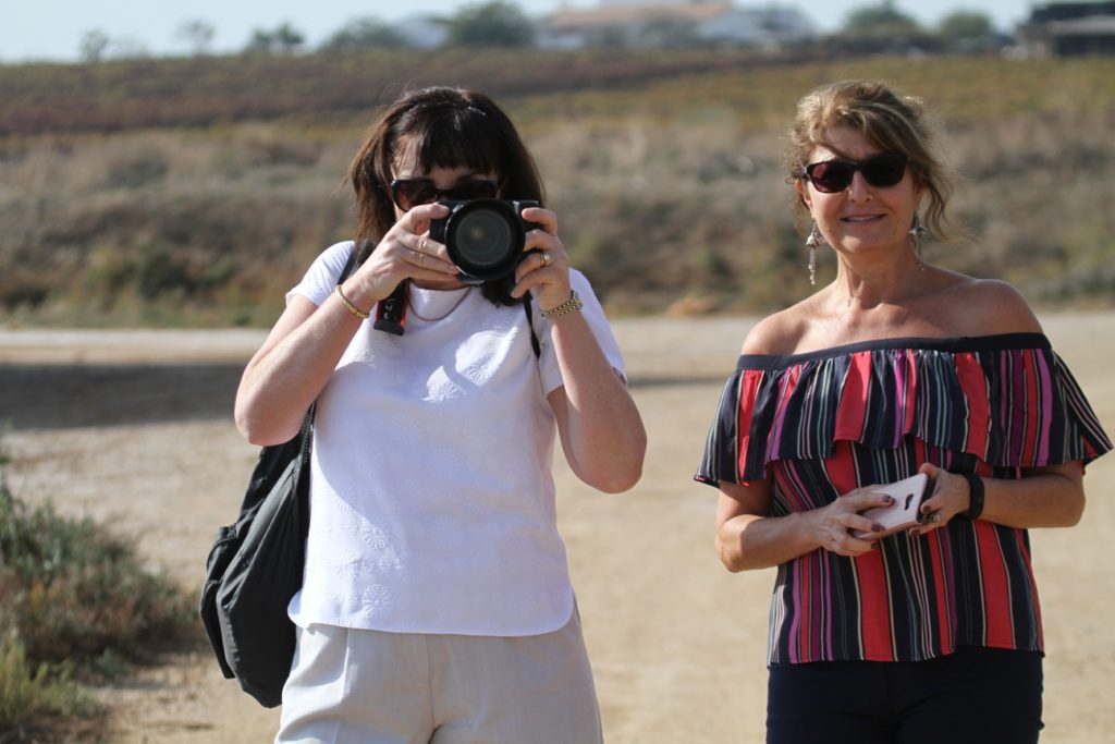 Two women taking photos on the beach in Portugal