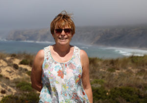 Woman in white top in from of coastline