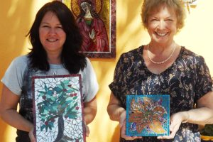 women holding mosaic art works in the sun