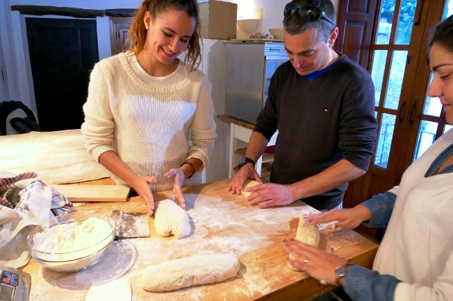 Guests kneading dough to make sourdough loaves