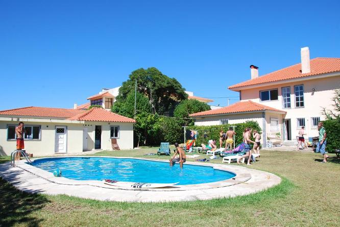 Surfers sitting by the pool at hostel on holiday in Portugal
