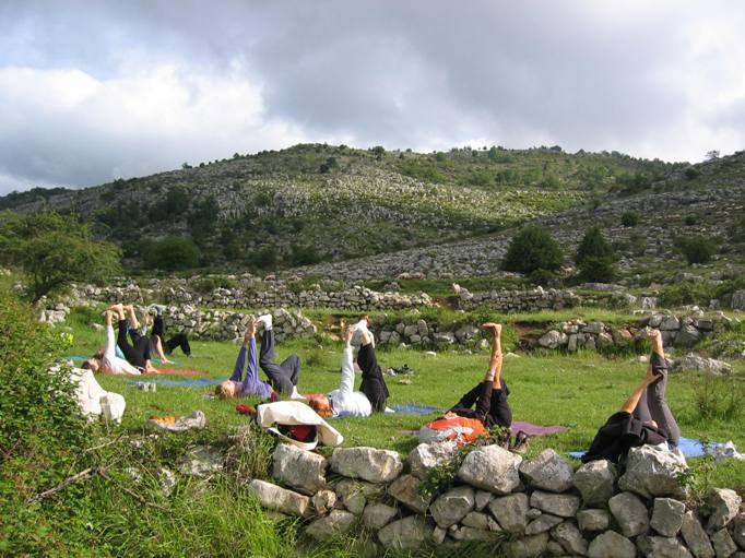 People doing yoga outdoors in a field in France