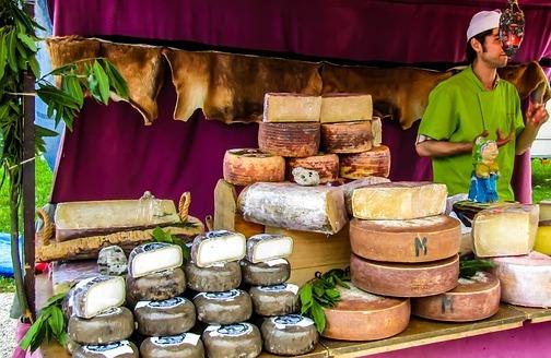 man at market stall selling cheese