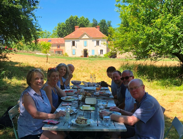 Holiday guests enjoying lunch outside in garden of French farmhouse