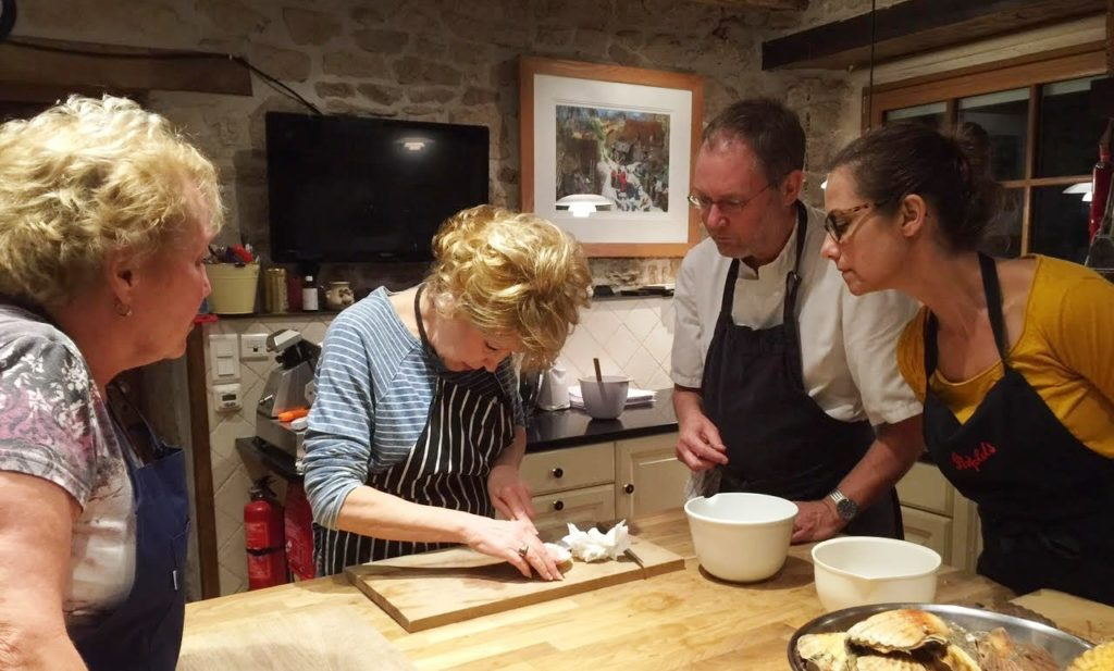 French chef guiding cookery students to open oysters
