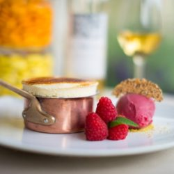 French souffle dessert plated with raspberries and ice cream