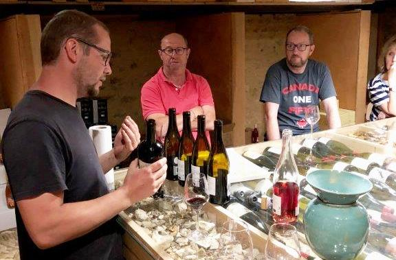 Wine producer leading wine tasting seminar with bottles of wine