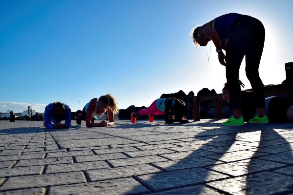 Fitness guests and instructor planking in the street in the sun