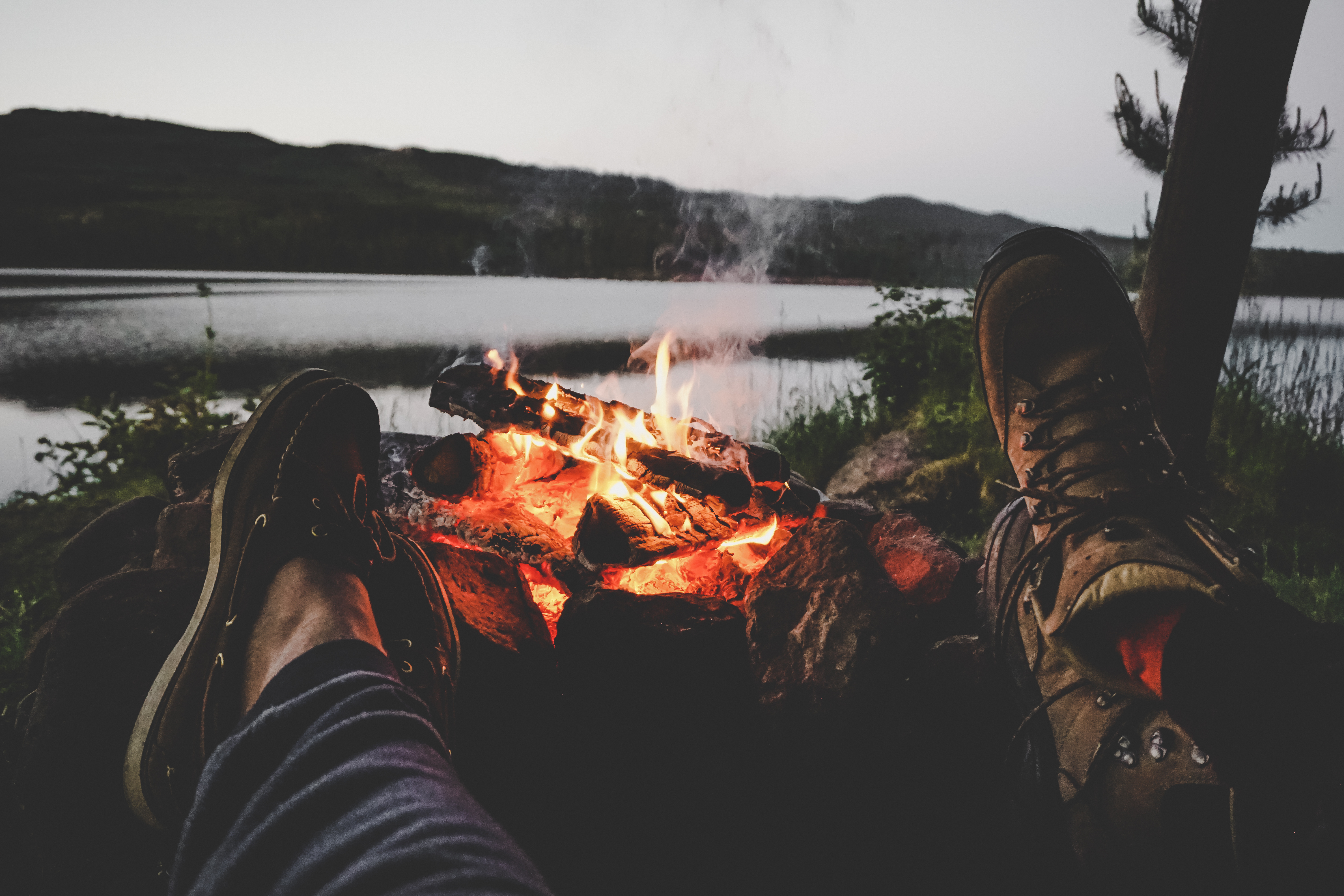 Couple warming their feet on camp fire