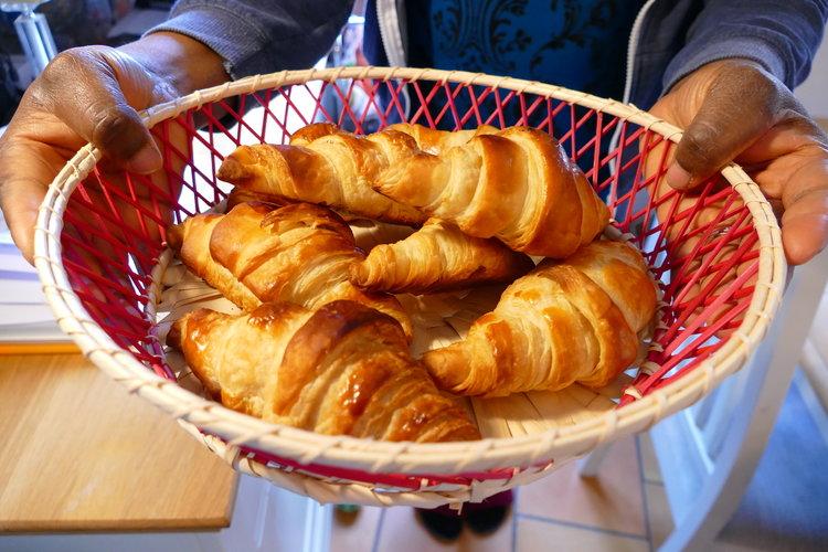 Hands holding a basket of freshly baked croissants