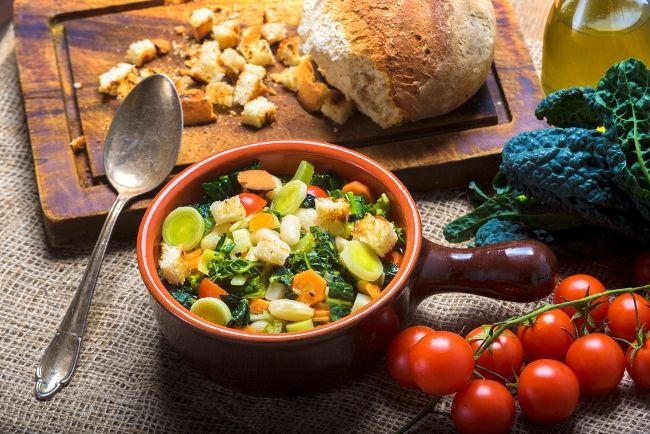 rustic bowl of ribollita soup with bread and tomatoes