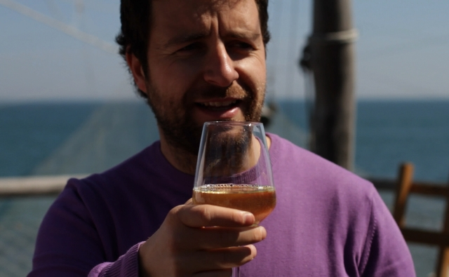 your guide Fabrizio holding glass of wine by the sea