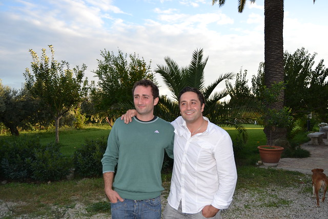 two brothers stand for photo against vineyard