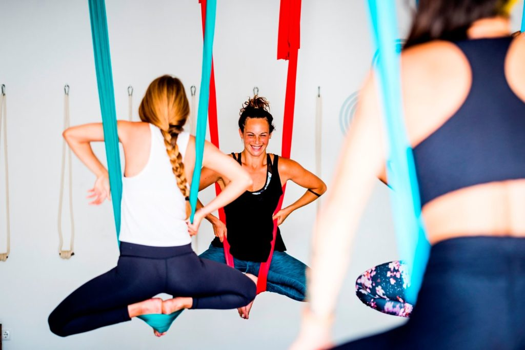instructor laughing in an aerial yoga class