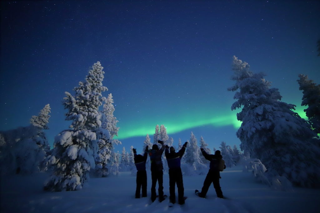 snowshoeing group admire northern lights