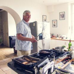 host Adam cooking in the kitchen