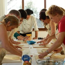 chef and guests rolling pasta dough from scratch