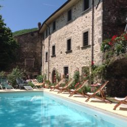 Tuscan palazzo and swimming pool with deck chairs