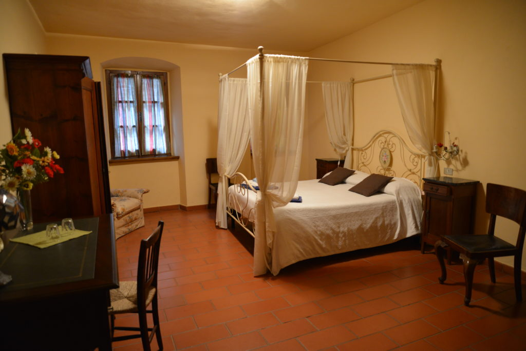 double bedroom with four post bed on cooking holiday in Tuscany