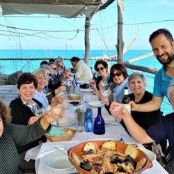 Italian cooking guests enjoy lunch by the sea