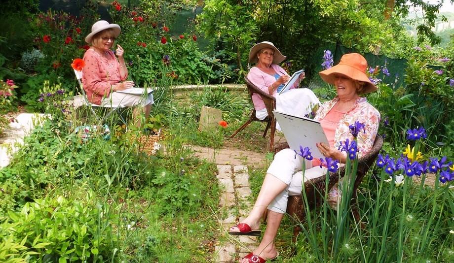three women painting in a garden