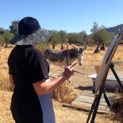 artist painting in Spanish field with donkey