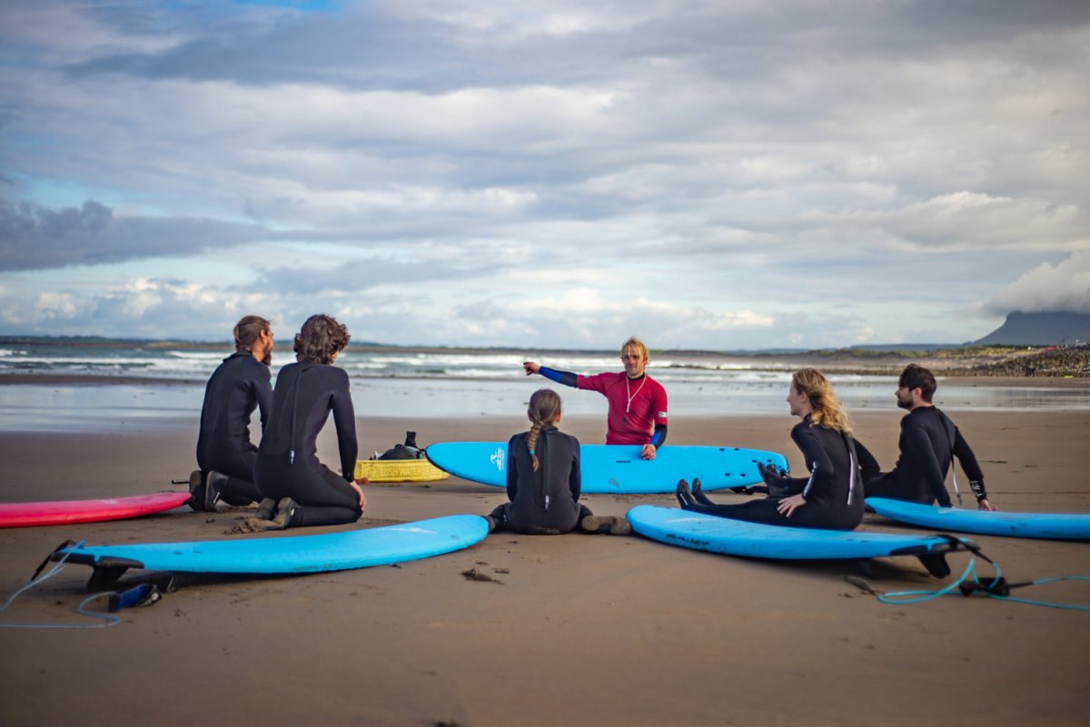 surfers and instructor talk on the beach
