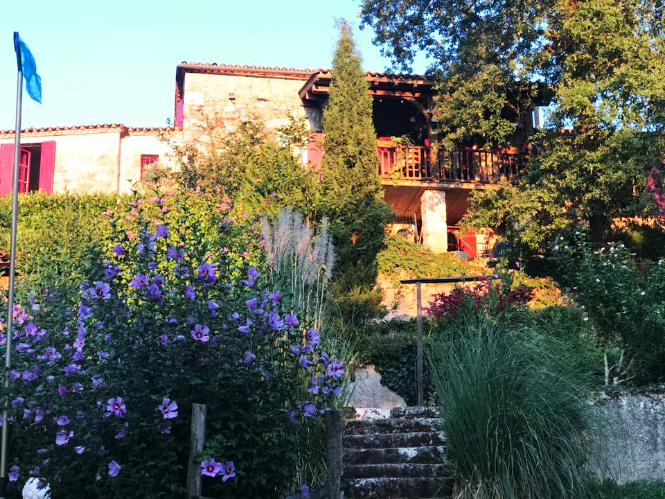 French farmhouse surrounded by plants and flowers