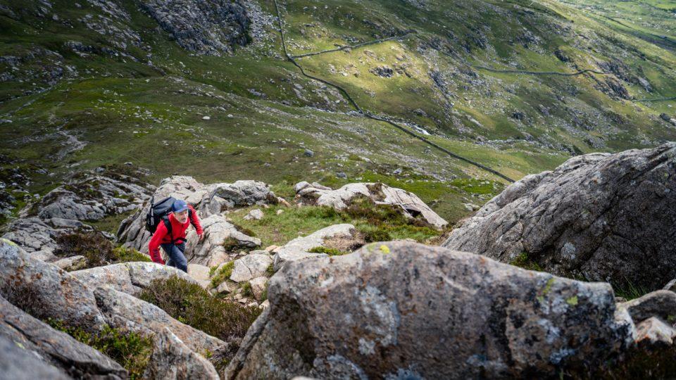 man hiking up rocks in green hills
