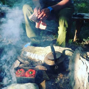 man cooking peppers on camp fire