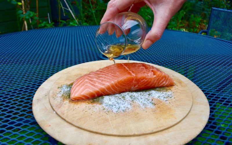 glass pouring oil over salmon fillet