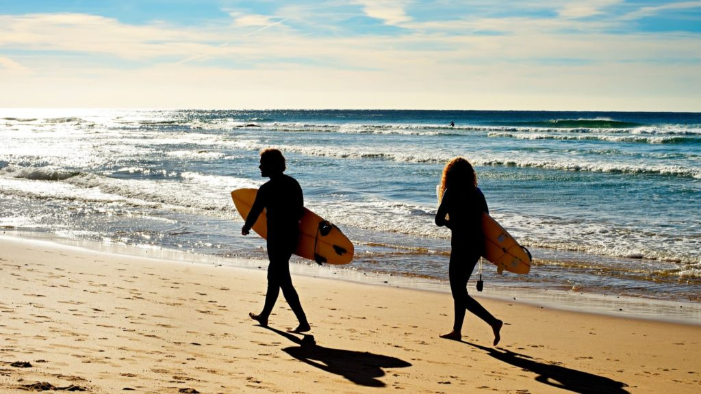 surfers on beach in portugal