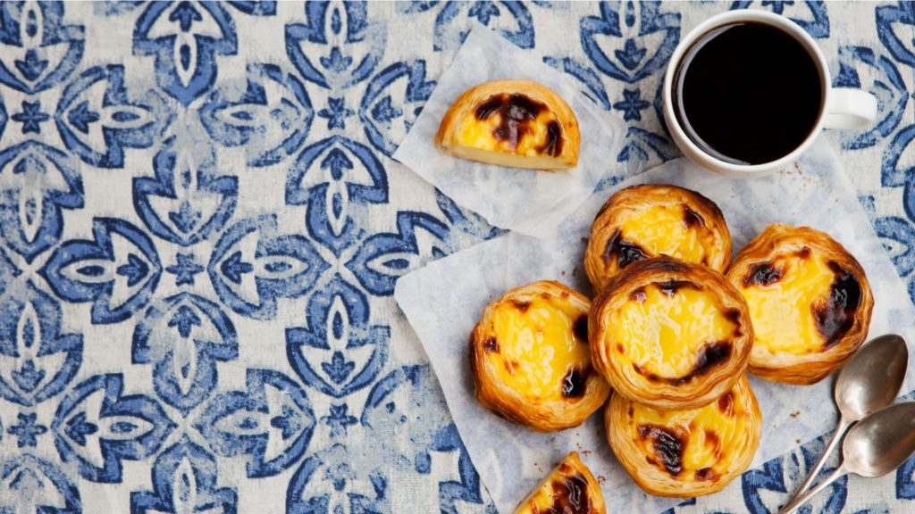 coffee and Portuguese tart on tiled table