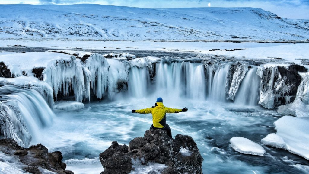 man looking at winter canyon in iceland