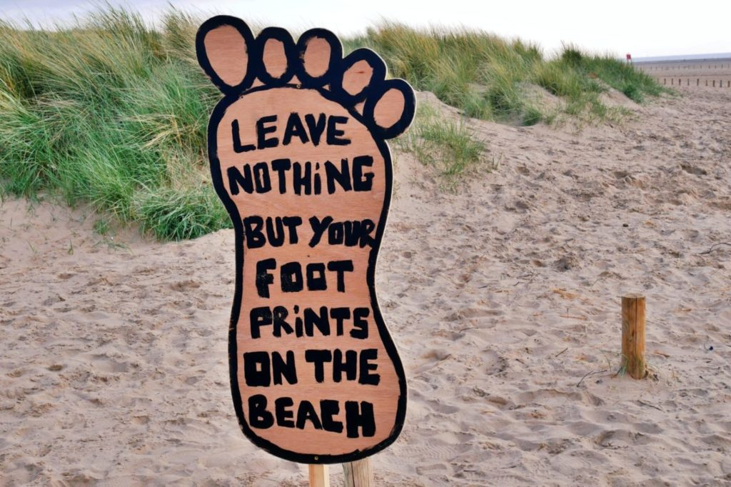 sign on a beach promoting responsible travel