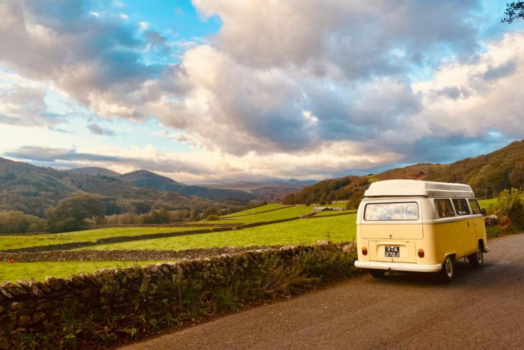 yellow campervan being driven in the lake district