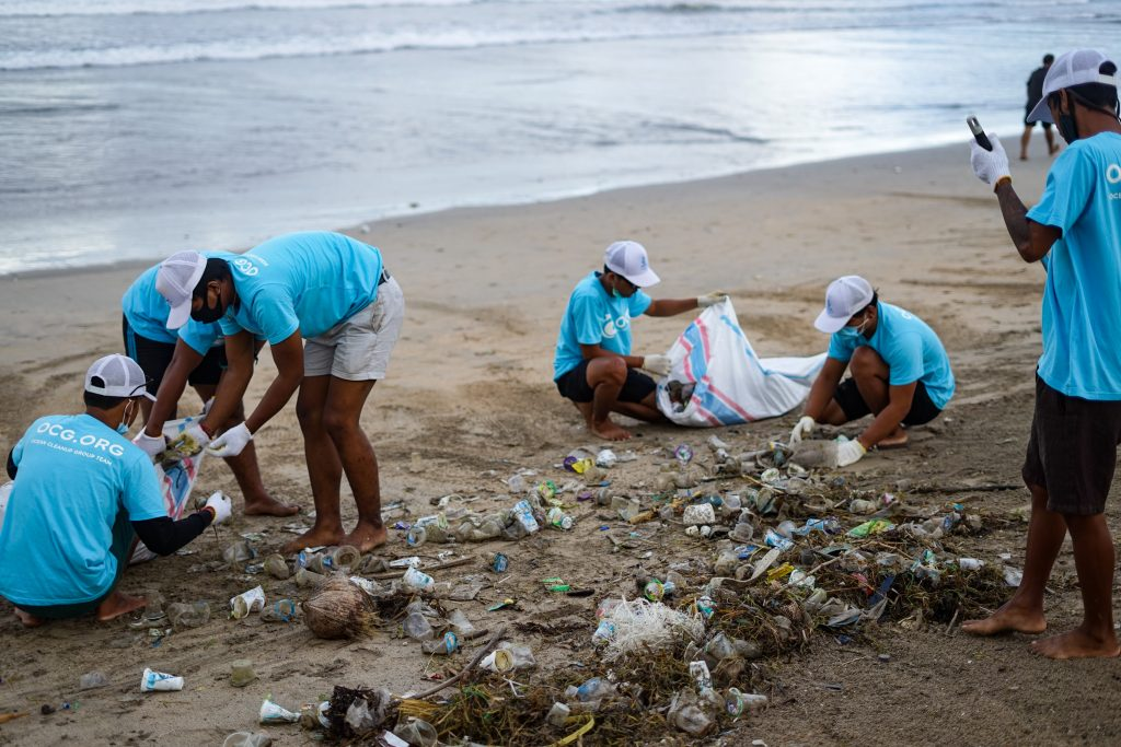 people cleaning plastic off a beach
