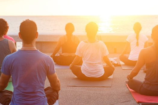 yoga lesson overlooking sea at sunset