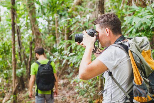 man taking photograph on jungle trek